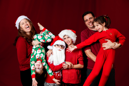 A silly family poses in a funny way for a Christmas portrait.  The mom laughs and holds her son upside down, one girl is wearing a Santa hat and beard while hugging her sister, while the dad holds another daughter who reaches out to her sisters. Stock Photo