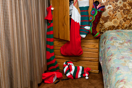 Six Christmas stocking hang on a dresser, ready to be discoverd on Christmas morning.  They are huge and most are stuffed. Stock Photo