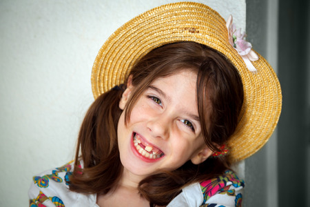 A cute young snaggletooth girl smiles. She is wearing a straw hat and is tilting her head to the side.
