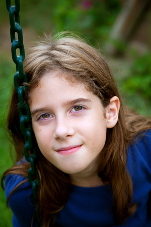 A confident and content tween girl sits on a swing, resting her head against the rubberized chain.  She looks at the camera with a close mouthed smile. Stock Photo