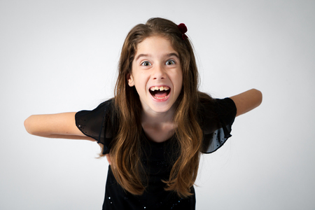 leaning forward: Portrait of a wide eyed, expressive girl on a white background.  She is leaning forward with an open mouth.