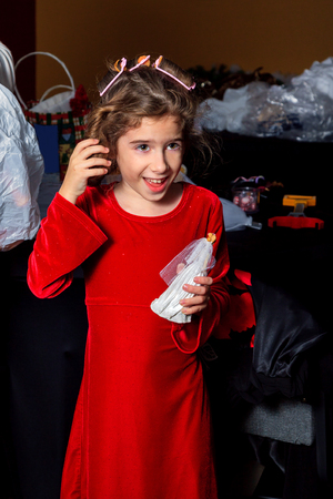 velvet dress: A young girl in a red, velvet dress feels the curl in her hair after a curler is removed.  Her facial expression is one of unexpected excitement or happiness. Stock Photo