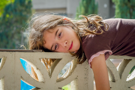 A young, tween girl, lays across a wall on a lazy day.  She is relaxing and soaking in the sun. Stock Photo