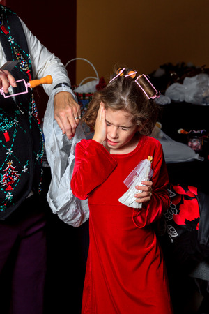 A little girl winces and puts her hand to her temple as a curler is pulled from her hair.  She is obviously in pain. Stock Photo