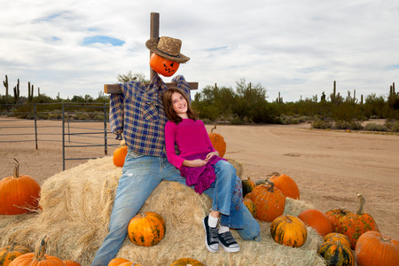 A young girl leans on a scarecrow as the two sit atop a pile of hay bales scattered with pumpkins before Halloween in the Arizona desert. Stock Photo