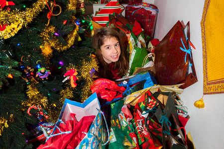 A little girl crawls out from under a pile of Christmas presents that almost swallow her.