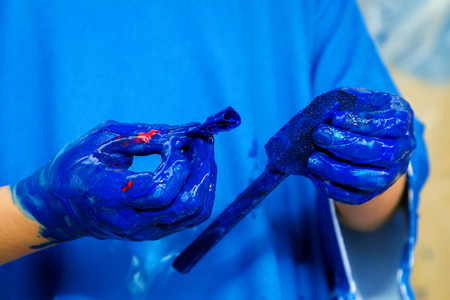 Close up view of the hands of a child wearing a blue apron.  The hands are covered with blue paint and holding a foam paint applicator.
