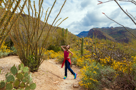 A silly tween girl poses in the Arizona desert on a cloudy day amidst saguaros, occotillos, and brittle brush.