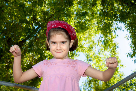A silly, young girl looks at the camera with a crazy facial expression.  She is holding her fists up, wearing a red bandana and is in front of backlit trees and a blue sky.