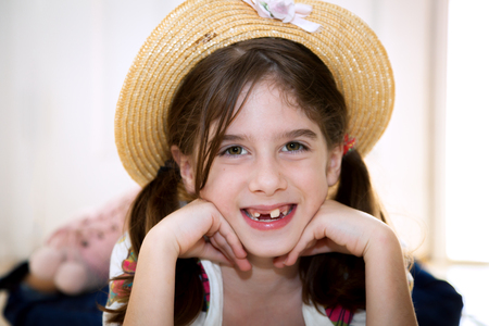 A cute, young, snaggletooth girl smiles with her chin on her hands.  She is wearing a straw hat and laying on her stomach.