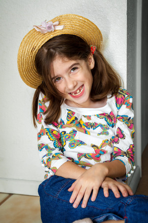 A cute young snaggletooth girl smiles with her while leaning up against a wall with hands crossed at her wrists. Stock Photo