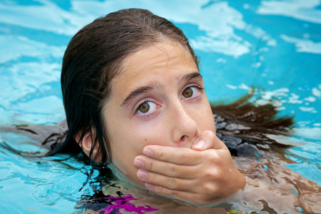 A tween girl in a swimming pool covers her mouth with her hand.  She is embarrassed to have her crooked teeth show in pictures.  She looks a bit surprised or scared. Stock Photo