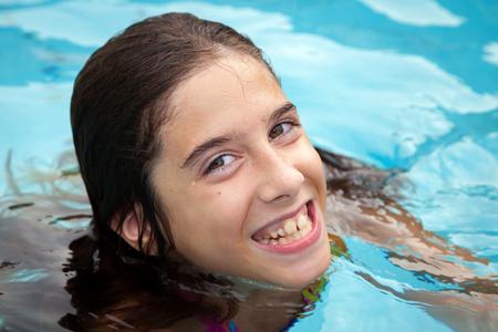 スイミング プールで幸せなトゥイーン ガールは、曲がっている歯で笑顔します。 彼女は冷たいので、彼女の唇と歯茎がわずかに青です。