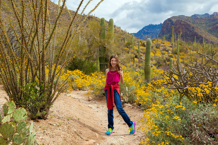 A young girl turns around to look back on an Arizona hiking trail in the middle of a blooming desert.
