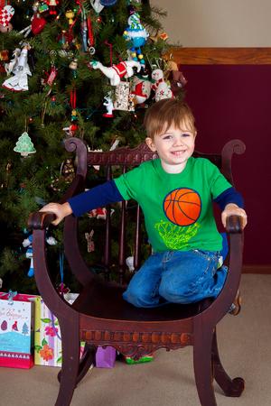 愛らしい少年は満面の笑みとアンティークの椅子でひざまずきます。 彼は前に飾られたクリスマス ツリーです。