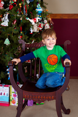 An adorable little boy kneels in an antique chair with a huge smile.  He is in front of a decorated Christmas tree.
