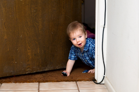 A baby boy in a plaid shirt peeks through a doorway while playing with two toy cars.  One is a police car. Stock Photo