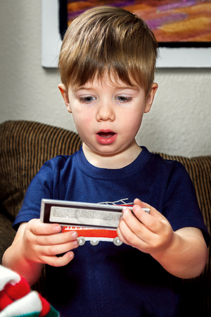 A cute little boy looks at something he has pulled out of his Christmas stocking.  His eyes are wide and his mouth is open in surprise.