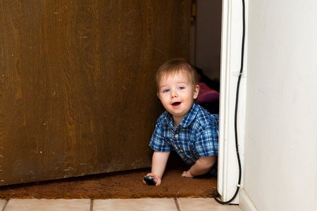 A baby boy crawls through a doorway with a smile and two toy cars in his hands.