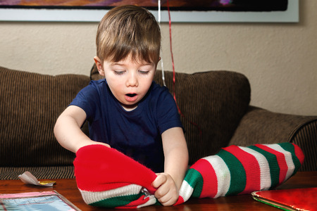 A little boy digs into his Christmas stocking with a look of excitement and wonder on his face.