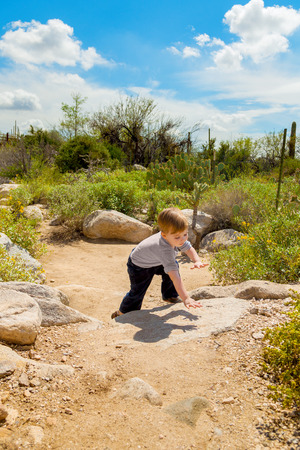 A cautious little boy hiking in the desert bends over to climb some low rocks on a trail.