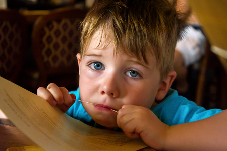 A tired and sad little boy sits chewing on a rubber band that is around a restaurant menu.  He looks up with pleading, blue eyes. Stock Photo