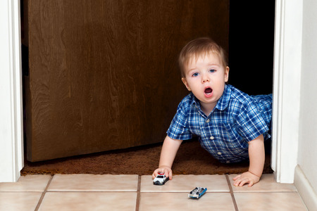 A baby boy crawls through a doorway while playing cars.  He has a police car in hand and a blue car lays upside down ahead of him.  He looks shocked and amazed with an open mouth and big eyes. Stock Photo