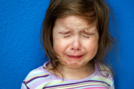 tearful: A little girl whose Chicken Pox are just starting to show stands crying her eyes out.  She looks so sad with tight clenched eyes spouting tears.