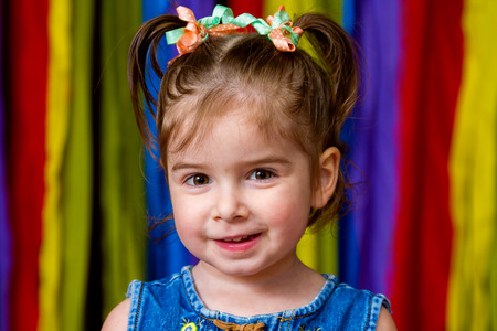 Portrait of an adorable girl with a great, happy expression stands in front of a rainbow background.  She has pig tails with ribbons. Stock Photo