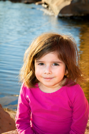A cute little girl sits slouching by a pond on a sunny day.