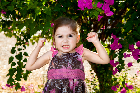 Little girl showing how strong she is by flexing.  She is using all of her facial muscles to flex as well and has her best, gritted teeth, beast mode face on.