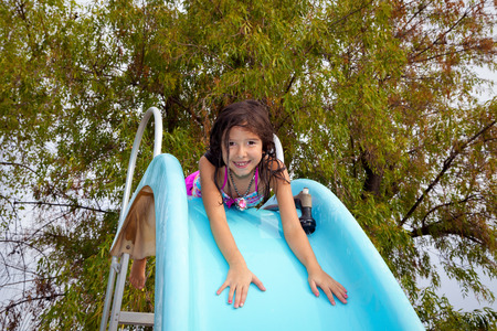 lays down: A little girl lays on top of a pool slide and is about to slide down on her tummy.  She smiles and has a hose next to her to wet the slide down. Stock Photo