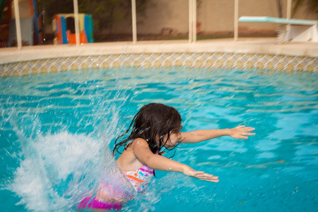 puffed cheeks: A young girl flying into the water backwards from a pool slide.  Her arms are spread out in front of her and her cheeks are puffed out to hold her breath.  The water is splashing all around her and there is copy space.