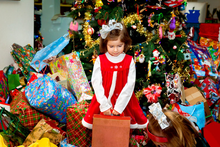 A young girl with a big, silver bow, and Santa dress stands holding a box in front of a huge Christmas tree and giant pile of presents.