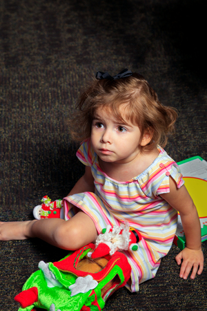 inquisitively: A young girl sits on a floor looking off to the distance inquisitively.  She is playing with Christmas toys.