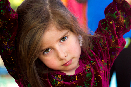 An irritated little girl gives an intense look.  She has her arms up and is leaning on something with her head cocked to the side, looking at the viewer with a furrowed brow and intense eyes. Stock Photo