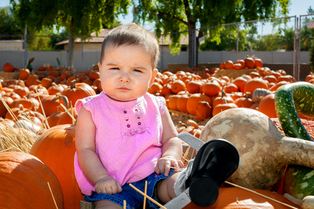 A skeptical looking baby sits atop a batch of pumpkins in a pumpkin patch.  She looks casual, confident in herself, yet unsure of her surroundings.  She is wearing a special brace for a club foot.