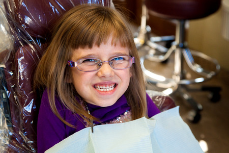 An adorable, little girl sits grinning in a dentist chair.  She looks happy and excited. Stock Photo