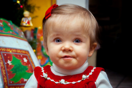 A surprised looking baby stares at the camera with wide eyes on her first Christmas morning.