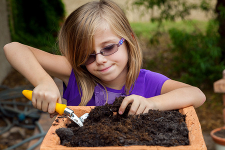 An adorable little girl digs in potting soil, making it ready to plant some flowers.  She has a sweet, closed mouth smile.