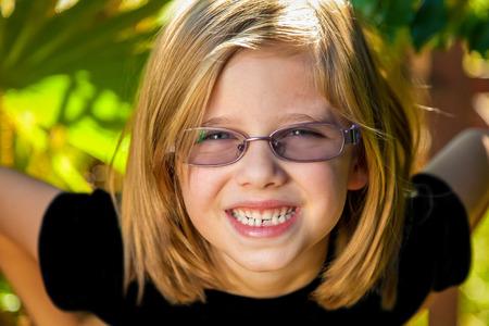 若い女の子は彼女の腰に大きな笑顔と彼女の手で前方に傾いています。 彼女は金髪で、眼鏡をかけてる。 リリースされたモデル。