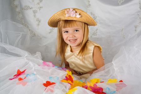 A young blue eyed girl smiles for a portrait.  She is dressed in a gold hat and dress that match her golden hair.  There is tulle in front of her with fake flower petals sprinkled in, and a fancy, white backdrop behinde her.