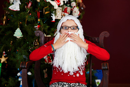A young girl in a Santa Claus hat and beard looks startled and covers her mouth with wide, blue eyes.
