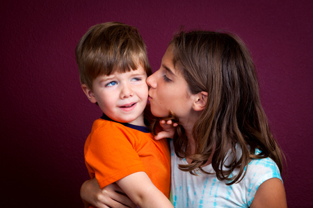 A little boy looks repulsed as he tries to recoil from a kiss his older sister is giving him.
