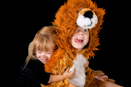 Two sisters in costumes being cute and silly.  A little, blond cat hugs her older sister the lion.  The lion has her tongue out and is making a funny face.