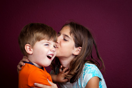 disgusted: An older sister kisses her little brother on the cheek as he pushes her away with a disgusted look on his face. Stock Photo