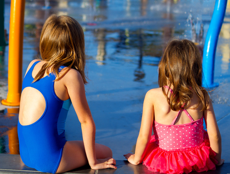elbow pad: View of the backs of two young sisters in swim suits as they sit and look at a splash pad.  The late afternoon sun is shining on them.  There is copy space.