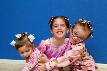 silliness: Three sisters sit on a linoleum floor wearing pajamas and curlers.  They have on pink pajamas and are hugging each other. Stock Photo