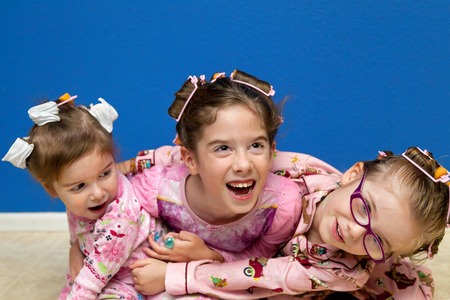 silliness: Three silly sisters, a little hyper before bedtime, hug in a pile on the floor while wearing curlers in their hair.  They are ready for bed in their pajamas.