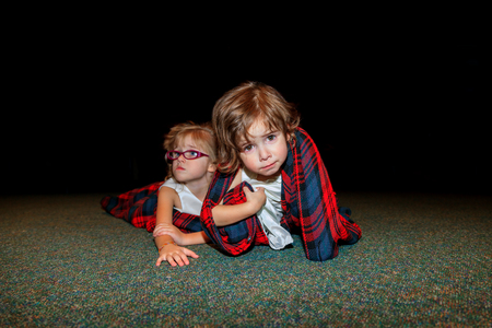 wiped out: Two flower girls lay on the floor in a blanket at the end of a busy wedding day, after the reception.  The youngest crawls toward the camera with a sad look and messy face. Stock Photo